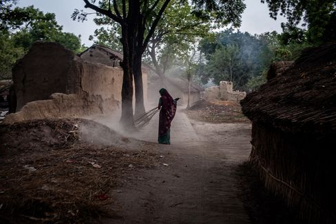 A villager sweeps the streets in Auar Village. Photographer: Sanjit Das/Bloomberg
