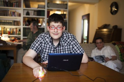 Alonso Arroyo, aged 12, center, plays on his PC laptop at the family home in Madrid. Photographer: Angel Navarrete/Bloomberg