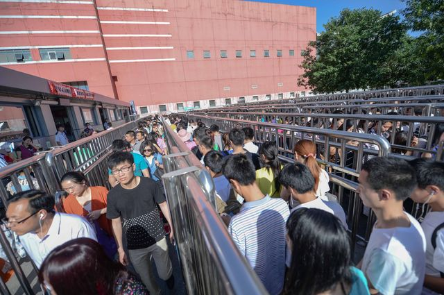 Passengers queuing up outside a Beijing subway station to go through a security check. Photographer: STR/AFP/Getty Images.