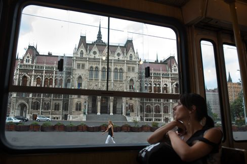 A customer looks through the window of a tram as it passes the parliament building on Kossuth square in Budapest. Photographer: Akos Stiller/Bloomberg