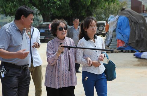 Victoria Li, a professor at the University of California, in sunglasses and with the aid of a walking stick, tour a village primary school in Changning county near Baoshan City, Yunnan province. Photographer: Daryl Loo/Bloomberg