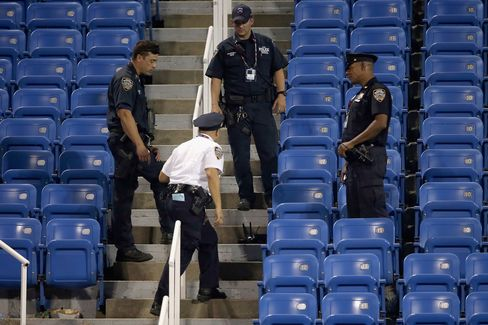 Police stand guard next to a drone after it crashed into the stands in Louis Armstrong Stadium during the during their Women's Singles Second Round match between on Day Four of the 2015 US Open, on Sept. 3, 2015 in Queens, NY.