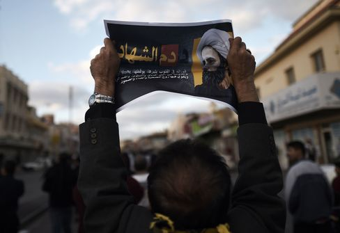 A protestor holds a poster bearing a portrait of cleric Nimr al-Nimr during a demonstration against his execution in the village of Jidhafs, west of Bahrain's capital Manama on Jan. 3, 2016.