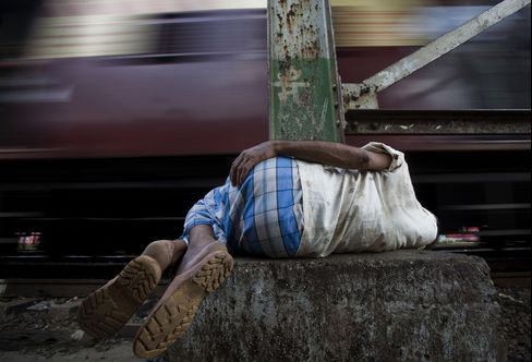 A man sleeps next to train tracks in the Dharavi slum area of Mumbai, India.