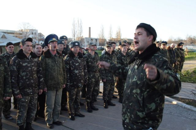 Ukrainian soldiers at the Belbek airbase oppose Russian special forces Saturday by singing the Ukrainian national anthem. Photographer: Oleg Klimov/Epsilon/Getty Images