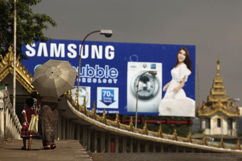 Pedestrians walk along the side of a road near an advertisement for Samsung Electronics Co. washing machines in Yangon, Myanmar. Samsung said it was targeting a 50 percent jump in sales of home appliances such as fridges and washing machines over three years. Photographer: Dario Pignatelli/Bloomberg
