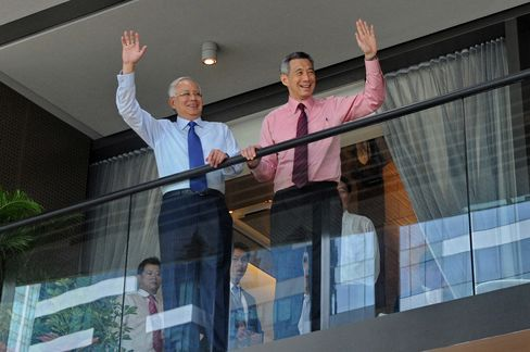 "Najib Razak, Malaysia's prime minister, left, and Lee Hsien Loong, Singapore's prime minister, wave from the balcony of a showroom during the Marina One unveiling ceremony in Singapore on Feb. 19, 2013. ""He is someone I can do business with,"" said Najib of his counterpart in an April 17 interview. Photographer: Roslan Rahman/AFP/Getty Images"