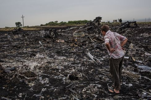 A man looks at debris from Thursday's Malaysia Airlines plane crash in Grabovka, Ukraine on July 18, 2014. Photographer: Brendan Hoffman/Getty Images