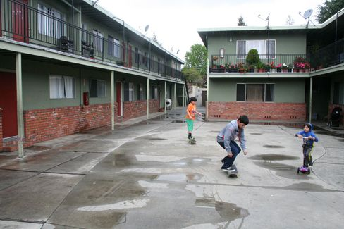 Ivan Lopez, 13, and his brothers Eduardo, 10, and Brandon, 3, play outside their building, which is owned by Equity Residential in East Palo Alto, California. Photographer: John Gittelsohn/Bloomberg