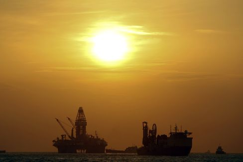 The Transocean Development Driller III, left, works to drill the primary relief well during sunrise at the BP Plc Macondo well site in the Gulf of Mexico off the coast of Louisiana in July 2010. Photographer: Derick E. Hingle/Bloomberg