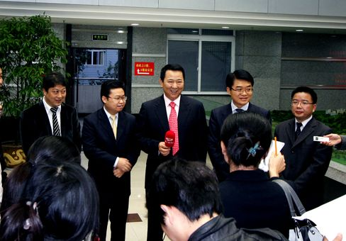 This file photo from 2009 shows Liu Han, third from right, founder of the Sichuan Hanlong Group as he is interviewed during the opening ceremony for the first solar streetlamp system in Dazu county, Chongqing, on Nov. 9 2009. Source: Imaginechina