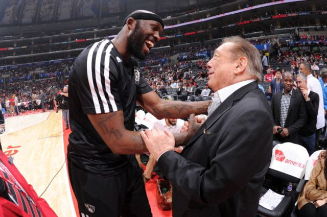 Donald Sterling, partially surrounded by Reggie Evans.Photographer: Andrew D. Bernstein/NBAE via Getty Images