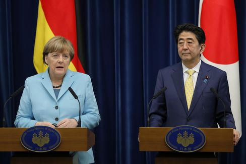 Angela Merkel, Germany's Chancellor, left, speaks as Shinzo Abe, Japan's prime minister, looks on during a news conference in Tokyo, Japan, on Monday, March 9, 2015.