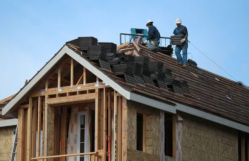 Construction workers move roofing tiles onto the roof of a home in a housing development in Dublin, California. Photographer: Justin Sullivan/Getty Images