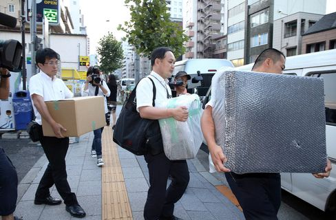 Police officers carry pieces of evidence from the house of Mark Karpelès, head of defunct Bitcoin exchange Mt. Gox, in Tokyo on Aug. 3.