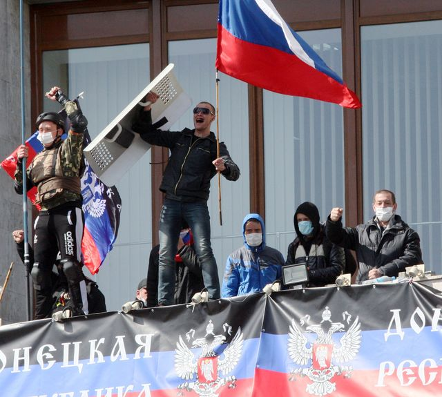 Pro-Russian activists who seized the main administration building in the eastern Ukrainian city of Donetsk hold theRussian flag and the flag of theso-called Donetsk Republic on April 7. Photographer: Alexander Khudoteply/AFP/Getty Images