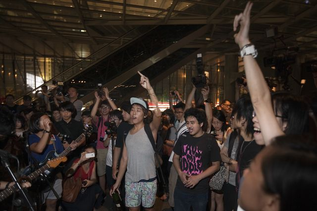 Young people listen to heavy metal music during an Occupy Hong Kong protest in the open-air plaza beneath HSBC Holdings Plc's Asian headquarters in Hong Kong. Photographer: Daniel J. Groshong/Bloomberg
