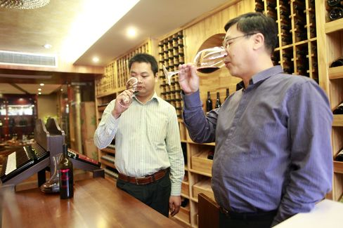 Lin Tiangui, a representative for Winston Wines Pty, left, and Huang Yongqiang, a store manger for Winston Wines, sample wine at the company's store in Shanghai. Photographer: Qilai Shen/Bloomberg