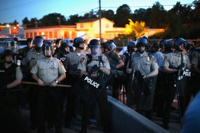 Police stand watch as demonstrators protest the shooting death of teenager Michael Brown inFerguson, Missouri.