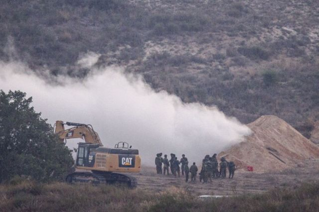 Israeli soldiers spray gas ata tunnel used by Hamas militants to infiltrate Israeli lines.