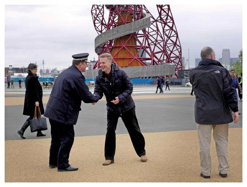 Deighton, right, greets Assistant Metropolitan Police Commissioner Chris Allison, who is in charge of Olympics security. In the background is the Anish Kapoor-designed ArcelorMittal Orbit tower.
