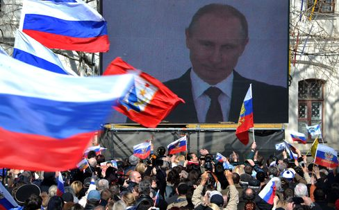 People Wave Russian Flags as President Putin is seen on a Screen
