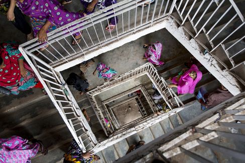Workers leave for their lunch break in a building that houses garment factories in Dhaka, Bangladesh. Photographer: Jeff Holt/Bloomberg
