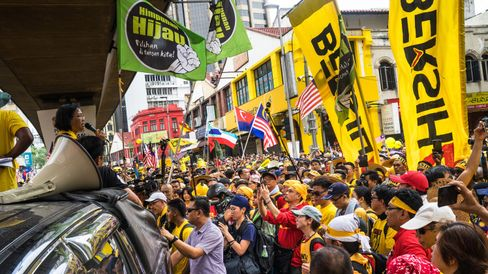 An organizer for the Coalition for Clean and Fair Elections rally, also known as Bersih, speaks as protesters wave banners.