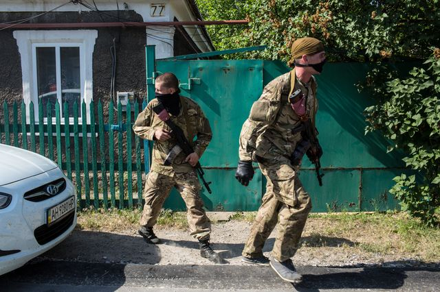 Pro-Russian fighters outside the Donetsk airport Monday.Photographer: Brendan Hoffman/Getty Images
