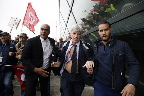 Security officers escort Air France's Pierre Plissonnier away, after employees invaded Air France offices.