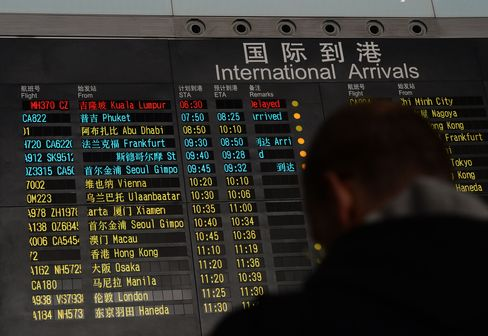 A man stands beside the arrival board showing the Malaysian Airline System Bhd. flight MH370, top in red, at the Beijing Airport on Saturday, March 8. Photographer: Mark Ralston/AFP/Getty Images