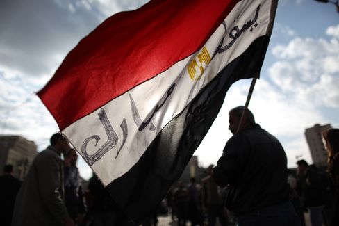 Protestors carry an Egyptian flag through Tahrir Square in Cairo, Egypt. While the markets in Cairo closed after the benchmark EGX 30 Index tumbled 16 percent last week, overseas investors have been betting on a rally in Egyptian assets. Photographer: Peter Macdiarmid/Getty Images
