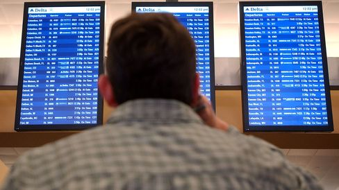 A Delta Airlines passenger reads the flight departure screens at Atlanta Hartsfield-Jackson International Airport.