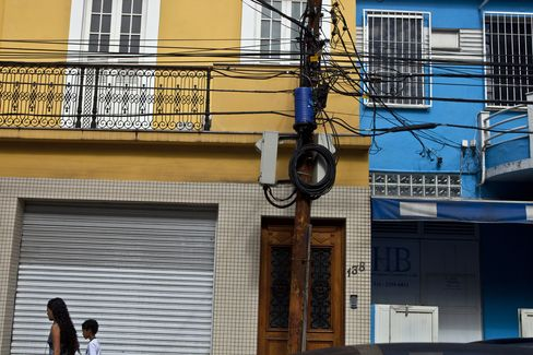 People Walk Past an Electricity Pole in Rio de Janeiro