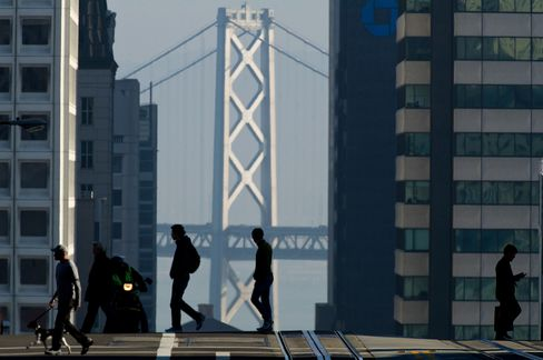 Pedestrians cross the street in front of the Oakland-San Francisco Bay Bridge in San Francisco, California. Photographer: David Paul Morris/Bloomberg