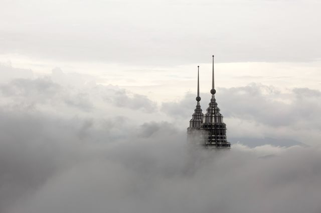 The pinnacles of the Petronas Twin Towers protrude through low clouds in Kuala Lumpur.