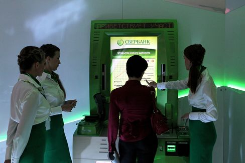 Employees operate a lie-detecting automated teller machine (ATM) on the OAO Sberbank stand at the St Petersburg International Economic Forum (SPIEF), in St Petersburg, Russia. Photographer: Andrey Rudakov/Bloomberg