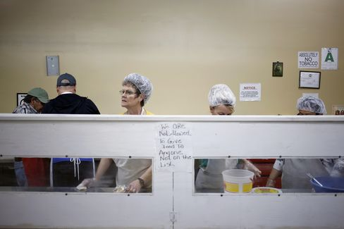 Volunteers serve dinner at the Christ's Hands Soup Kitchen and Food Pantry in Harlan, Kentucky. In the coal region of eastern Kentucky, extra money is hard to come by. Photographer: Luke Sharrett/Bloomberg