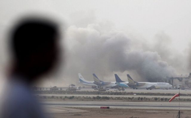 A Pakistani man watches as smoke rises after militants launched an assault early Monday morning on Karachi's international airport.