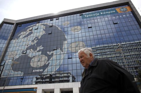 A pedestrian passes a world map design with time zones for Nicosia, Athens, Sydney and New York on the facade of the headquarters of the Bank of Cyprus Plc in Athens. Photographer: Kostas Tsironis/Bloomberg