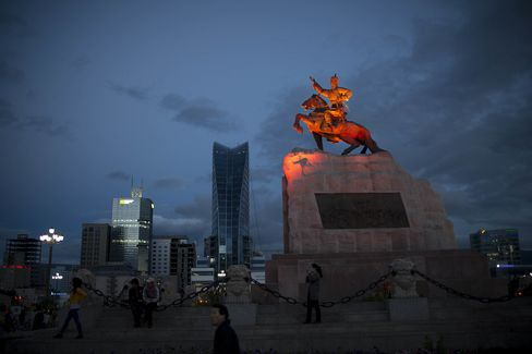 An illuminated statue of Damdid Sukhbaatar, right, stands on Chinggis Khaan Square.