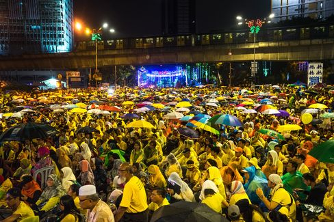 Protesters brave the rain as they gather in large numbers near the Merdeka Square on Aug. 30. Photographer: Sanjit Das/Bloomberg