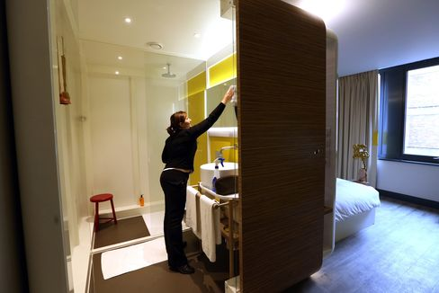 A Chambermaid Cleans the Bathroom of a Room at a Hotel in London