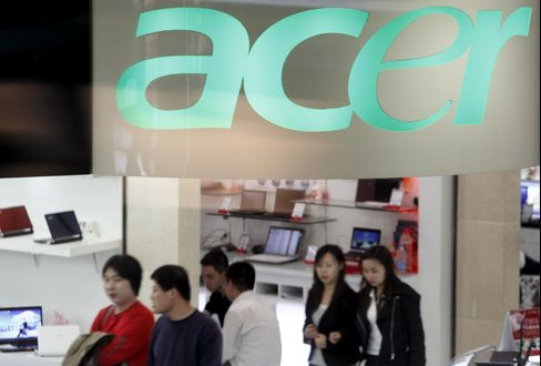 Shoppers walk past a store selling Acer Inc. products
