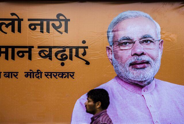 A pedestrian walks past a billboard for elections victor Narendra Modi.Photographer: Prashanth Vishwanathan/Bloomberg