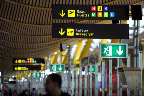 Signs hang at the departure gates at Barajas airport's terminal 4 in Madrid. Photographer: Denis Doyle/Bloomberg