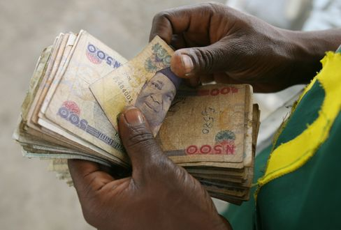 A Petrol Station Attendant Counts Nigeria's Naira Currency