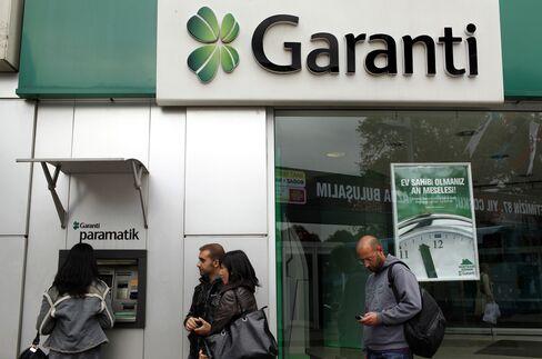 Customers wait at a Turkiye Garanti Bankasi ATM in Istanbul