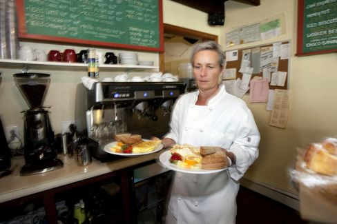Jennifer Cavallaro, owner of The Bee Hive Cafe, carries plates of food through her cafe in Bristol, Rhode Island, June 27, 2011. Photographer: Victoria Arocho/Bloomberg