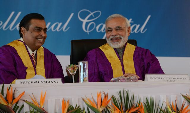 The campaign by India's corporate-owned media to promote Modi seems to have worked. Mukesh Ambani and Narendra Modi in October 2013. Photographer: Sam Panthaky/AFP/Getty Images